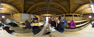 Chäsbrätel mit Rugenbräu: a melted cheese sandwich with a local beer, served in a cow barn avove Axalp in the Swiss Alps.  Click to view this panorama in new fullscreen window