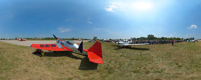 Jurgis Kairys' crew member taking a rest by his Juka plane during the air show in Kraków.  Click to view this panorama in new fullscreen window