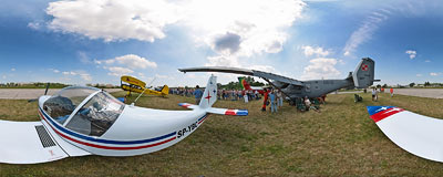 Air Show in Kraków: EV-97 Eurostar ultralight plane with a Polish navy's PZL M28 Bryza plane in the back.  Click to view this panorama in new fullscreen window